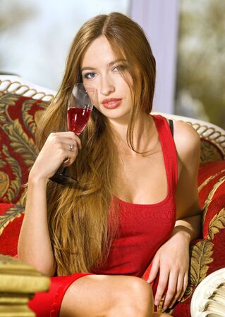 beautiful happy woman in red dress on a sofa with glass of champagne photo