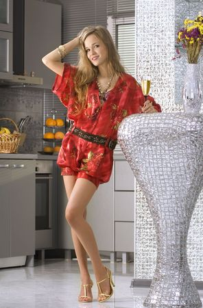 beautiful woman wearing red dress with glass of fizz in home photo