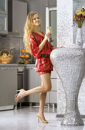 beautiful woman wearing red dress with glass of champagne in home photo