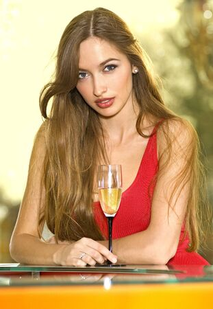 beautiful pretty woman in red dress on a sofa with glass of champagne photo