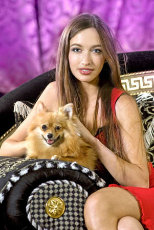 pretty girl on a black expensive sofa with doggie photo