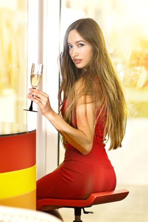 nicely: beautiful single woman in red dress with glass of champagne Stock Photo