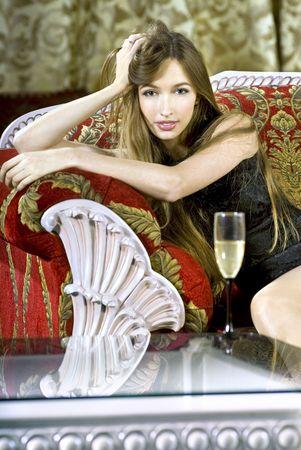 rijke vrouw: prachtige jonge rijke vrouw bijna een koffie tabel met glas fizz Stockfoto