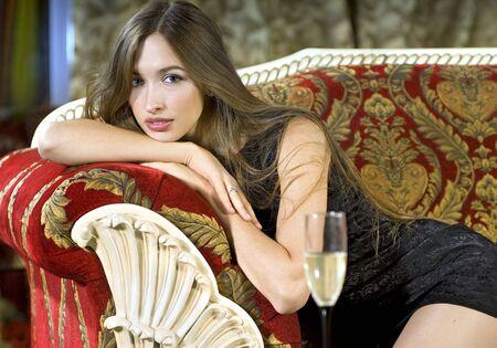 happy rich woman: bella donna bionda ricca su un divano rosso costoso