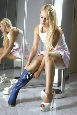 beautiful girl fits on a white boots in a boutique Stock Photo - 6016398