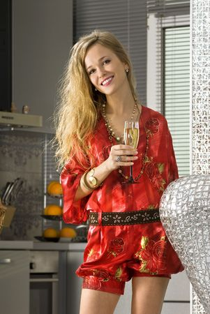 landlady: happy woman wearing red dress with glass of champagne in a kitchen  Stock Photo