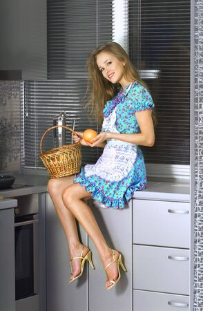 beautiful housewife with basket in the kitchen photo