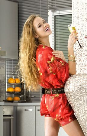 happy woman wearing red dress with glass of champagne in a kitchen Stock Photo - 6049537