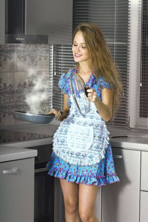 mistress: beautiful happy housewife with serving spoon in the kitchen