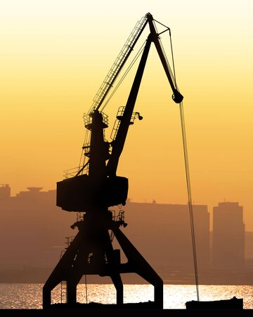 crane sit dramatically against a colorful sunset in a large shipyard Stock Photo - 6182885
