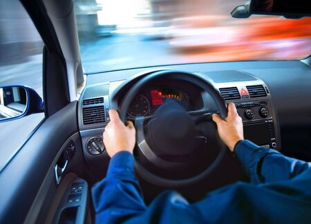 hands of driver that sits on drivers seat and turning wheel photo