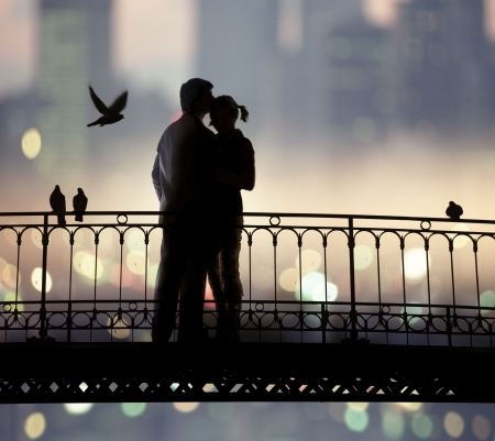 amorousness: silhouette of bridge and pair of lovers on city background Stock Photo