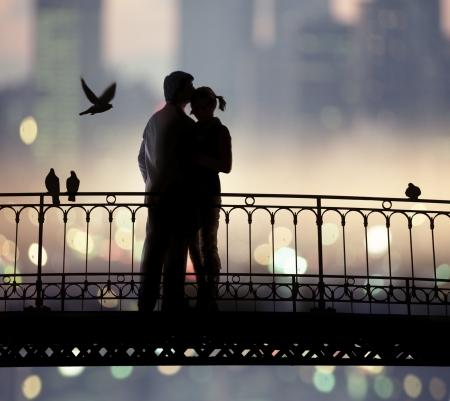 romantico: silueta de puente y la pareja de amantes en segundo plano de la ciudad