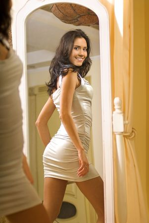 Portrait of woman in white dress she admires oneself in the looking-glass photo