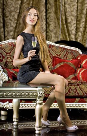 beautiful happy woman in red dress on a sofa with glass of champagne Stock Photo - 6236040