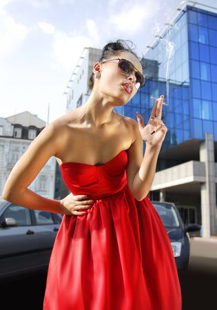 beautiful smoking lady in red dress near business building photo