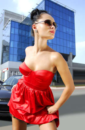 supercilious: beautiful independent brunette in sunglasses and red dress