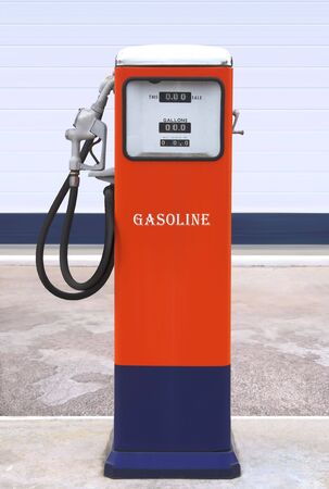 Ancient gas pump painted in bright dark blue and orange in the setting of an old gas station photo