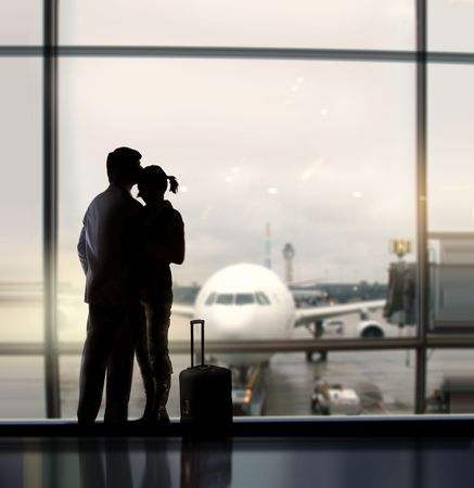 urban decline: silhouette of pair of lovers near the window in airport Stock Photo