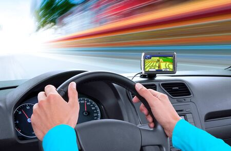 navigator on dashboard and hands of driver that sits on drivers seat