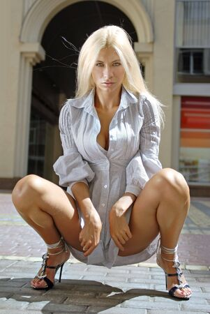 chemise: beautiful blonde in chemise sits on floor of shopping mall