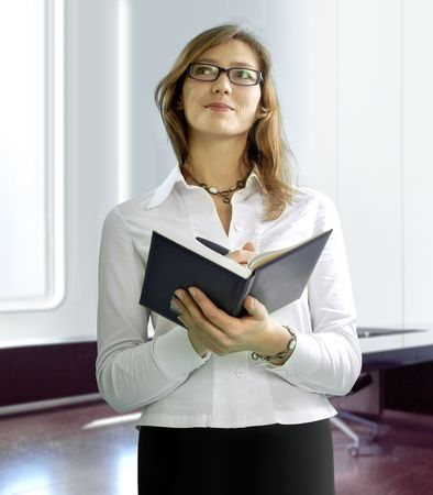 stockbroker: beautiful business woman with notebook in office building