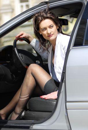 elegante: femme Brunette semble ronds et parcs de la voiture de retour Banque d'images
