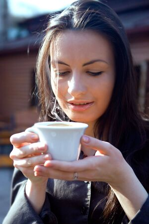 Portrait of beautiful brunette woman drinking hot cappuccino Stock Photo - 6778914