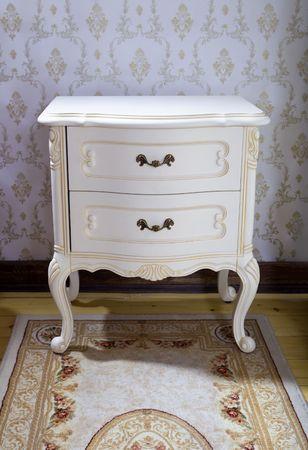 cassettiera: dettaglio del vintage comodino in legno con tre cassetti sul tappeto