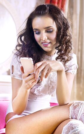 beautiful lovely woman with cell phone in luxury hotel room photo