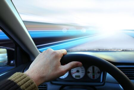 highroad: hand of driver that holds wheel and goes on road