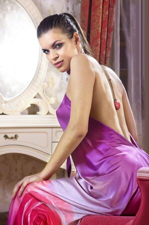 woman wearing pink dress in her room of luxury hotel photo