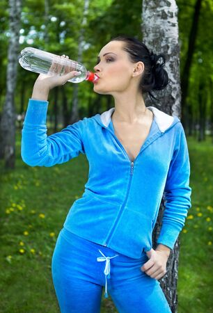 beautiful girl drinks water in park after sport  photo