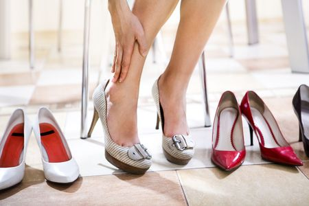 buying shoes: Close up de pies femeninos que se trat� sobre los zapatos en tienda