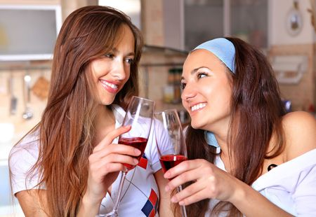 Happy women drinks red wine in the kitchen and talk about photo