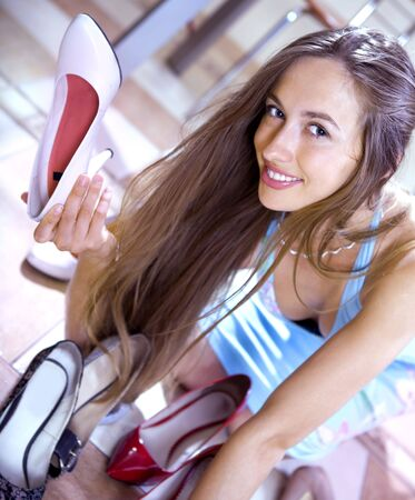 happy woman shopaholic with heap of shoes in shopping mall photo
