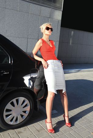blonde businesswoman near black car in the city photo