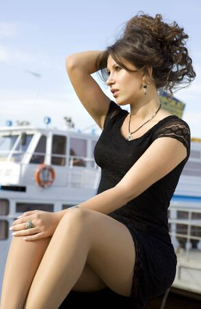 uncombed: beautiful brunette lady in black dress on mooring