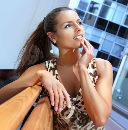 emotional beautiful brunette in white shorts on bench photo