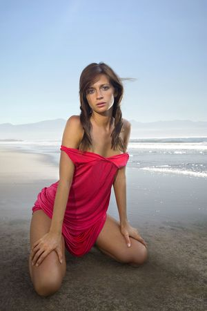 beautiful woman in red dress at sandy coast photo