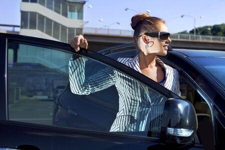 lean out: business woman in sunglasses near the car against city bridge