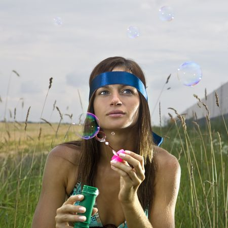 thoughtful young woman blowing soap bubbles in summer day photo