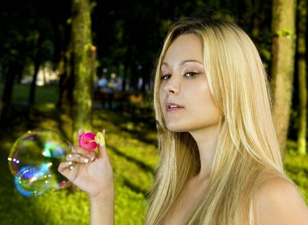 blonde young woman blowing soap bubbles in summer day photo