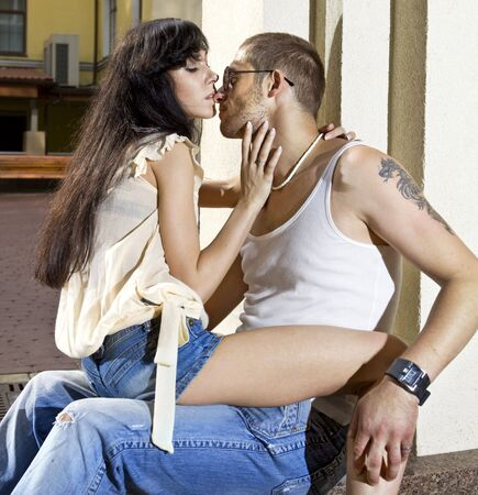 romantic hug: young couple on the street at summer day