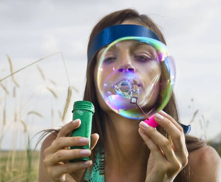 beauty young woman blowing soap bubbles in summer day photo