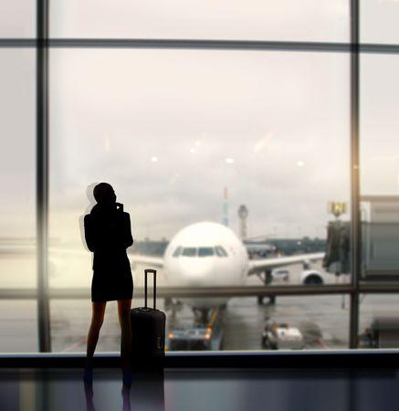 takeoff: silhouette di donna d'affari, che si aspetta di volo a bordo l'aereo in aeroporto Archivio Fotografico