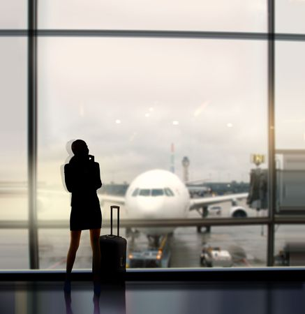 aboard: silhouette of businesswoman which expects flight aboard the plane in airport