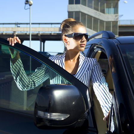 out of job: happy business woman in sunglasses near the car against city bridge Stock Photo