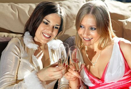 Happy women with glasses of wine talk about in drawing room photo