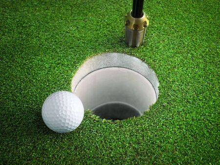 golf ball on lip of cup of lovely tropical golf course photo